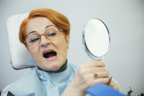 woman at dentist examines her teeth in mirror