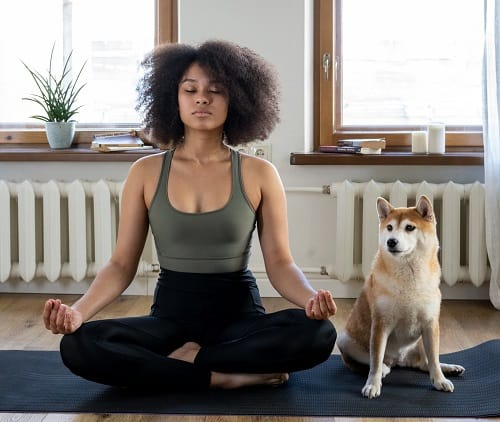 woman meditates with her dog